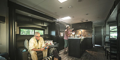 2020 Venture RV SportTrek Touring Edition STT343VIK Travel Trailer with man and woman in living room and kitchen