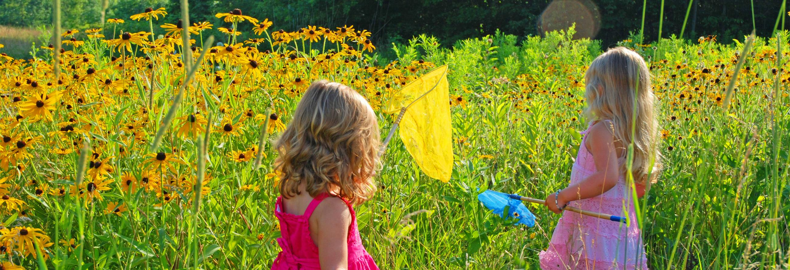 Girls in flower field with butterfly nets and their lightweight travel trailer